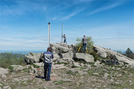 site surveyors with measuring equipment atop mountain
