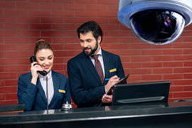 hotel receptionists on phone with video surveillance camera overhead