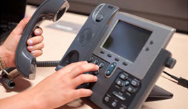 hands holding a VOIP phone and dialing