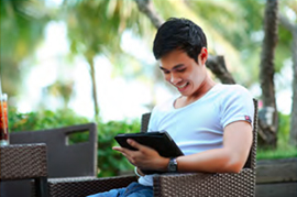 smiling man looking and holding tablet outside